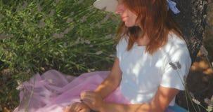 Mujer joven que pone y que duerme debajo del árbol almacen de metraje de vídeo