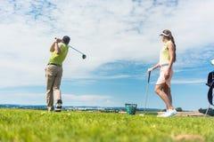 Mujer joven que practica el movimiento correcto durante clase del golf con a foto de archivo