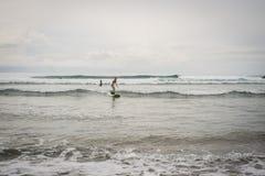 Mujer joven que practica surf en D r foto de archivo libre de regalías