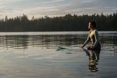Mujer joven que practica surf en luz del sol de oro imagenes de archivo