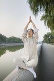Mujer joven que practica a Tai Ji, brazos aumentados, por el canal Imagen de archivo