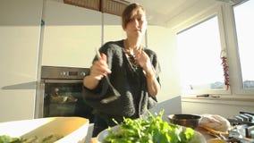 Mujer joven que prepara el almuerzo en la cocina metrajes