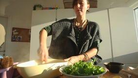 Mujer joven que prepara el almuerzo en la cocina almacen de metraje de vídeo
