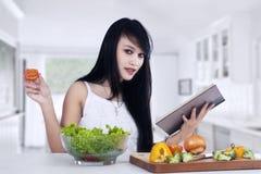 Mujer joven que prepara la ensalada Imágenes de archivo libres de regalías