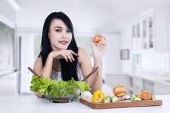 Mujer joven que prepara la ensalada de las verduras Imagen de archivo libre de regalías