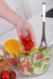 Mujer que prepara la ensalada sana en su cocina moderna Foto de archivo
