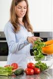 Mujer joven que prepara una ensalada con arugula Imagenes de archivo