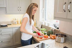 Mujer joven que prepara verduras Fotos de archivo