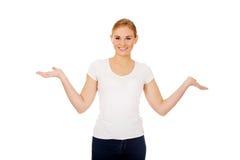 Mujer joven que presenta algo en las palmas abiertas Fotografía de archivo