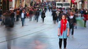 Mujer joven que presenta, calle muy transitada, gente que da une vuelta, HD almacen de metraje de vídeo