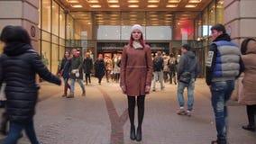 Mujer joven que presenta, calle muy transitada, gente que da une vuelta, HD