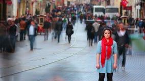 Mujer joven que presenta, calle muy transitada, gente que da une vuelta, 4K almacen de metraje de vídeo