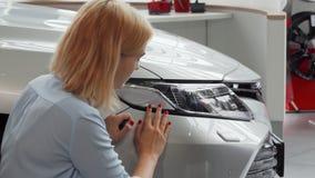Mujer joven que presenta cerca de su nuevo coche, llevando a cabo llaves almacen de video