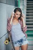 Mujer joven que presenta con el monopatín, verano, urbano, al aire libre Imagen de archivo