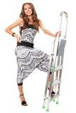 Mujer joven que presenta con el step-ladder en blanco imagenes de archivo