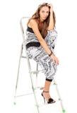 Mujer joven que presenta con el step-ladder en blanco fotos de archivo libres de regalías