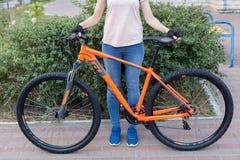 Mujer joven que presenta con la bicicleta en la imagen del estilo del deporte de la calle imágenes de archivo libres de regalías