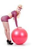 Mujer joven que presenta con la bola del ejercicio imagenes de archivo
