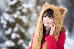 Mujer joven que presenta con smartphone al aire libre en invierno Fotos de archivo