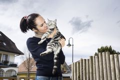 Mujer joven que presenta con un gato Fotografía de archivo libre de regalías
