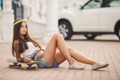 Mujer joven que presenta con un monopatín en la ciudad Imagen de archivo