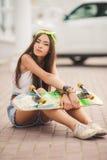 Mujer joven que presenta con un monopatín en la ciudad Foto de archivo libre de regalías