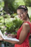 Mujer joven que presenta con una computadora portátil al aire libre Imagenes de archivo