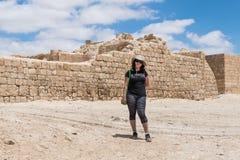 Mujer joven que presenta contra el contexto de las paredes de la fortaleza de la ciudad de la ciudad Avdat de Nabataean, situada  Imágenes de archivo libres de regalías