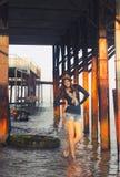 Mujer joven que presenta debajo del embarcadero Fotos de archivo libres de regalías