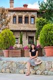 Mujer joven que presenta delante de una casa hermosa Foto de archivo