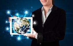 Mujer que presenta el globo de la tierra 3d en tableta moderna Foto de archivo