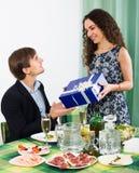 Mujer joven que presenta el regalo al hombre en la tabla foto de archivo