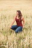 Mujer joven que presenta en campo de trigo Imagen de archivo libre de regalías