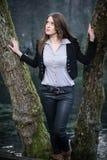 Mujer joven que presenta en el árbol Fotos de archivo