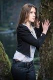 Mujer joven que presenta en el árbol Fotografía de archivo libre de regalías
