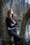 Mujer joven que presenta en el árbol Foto de archivo