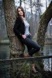 Mujer joven que presenta en el árbol Fotografía de archivo