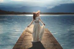 Mujer joven que presenta en el embarcadero del lago fotos de archivo