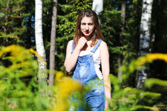 Mujer joven que presenta en el fondo, los arbustos del primero plano Imagen de archivo