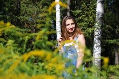 Mujer joven que presenta en el fondo, los arbustos del primero plano Fotos de archivo libres de regalías