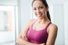 Mujer joven que presenta en el gimnasio Foto de archivo libre de regalías