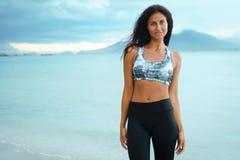 Mujer joven que presenta en la playa en ropa de deportes Modelo femenino en la orilla de mar foto de archivo libre de regalías