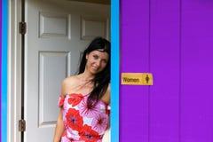 Mujer joven que presenta en la puerta de un lavabo imagenes de archivo