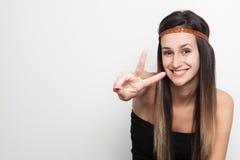 Mujer joven que presenta en un fondo blanco que hace paz Imagenes de archivo