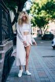 Mujer joven que presenta en un vestido blanco Foto de archivo libre de regalías