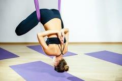 Mujer joven que presenta haciendo ejercicio aéreo de la yoga con la hamaca Imagen de archivo