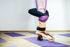 Mujer joven que presenta haciendo ejercicio aéreo de la yoga con la hamaca Imagenes de archivo