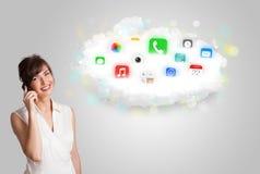 Mujer joven que presenta la nube con los iconos coloridos y los símbolos del app Foto de archivo