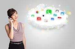 Mujer joven que presenta la nube con los iconos coloridos y los símbolos del app Imagenes de archivo