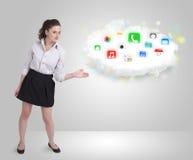 Mujer joven que presenta la nube con los iconos coloridos y los símbolos del app Foto de archivo libre de regalías